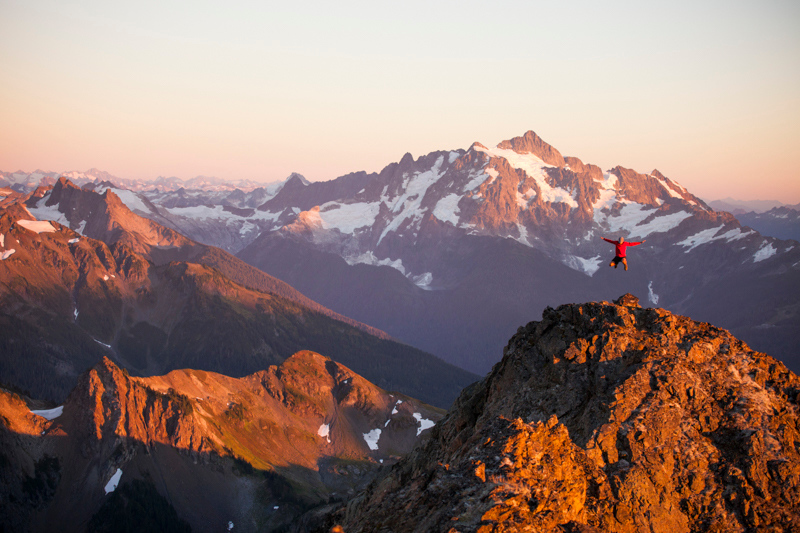 A man jumps off a rocky cliff  in North Cascades National Park.