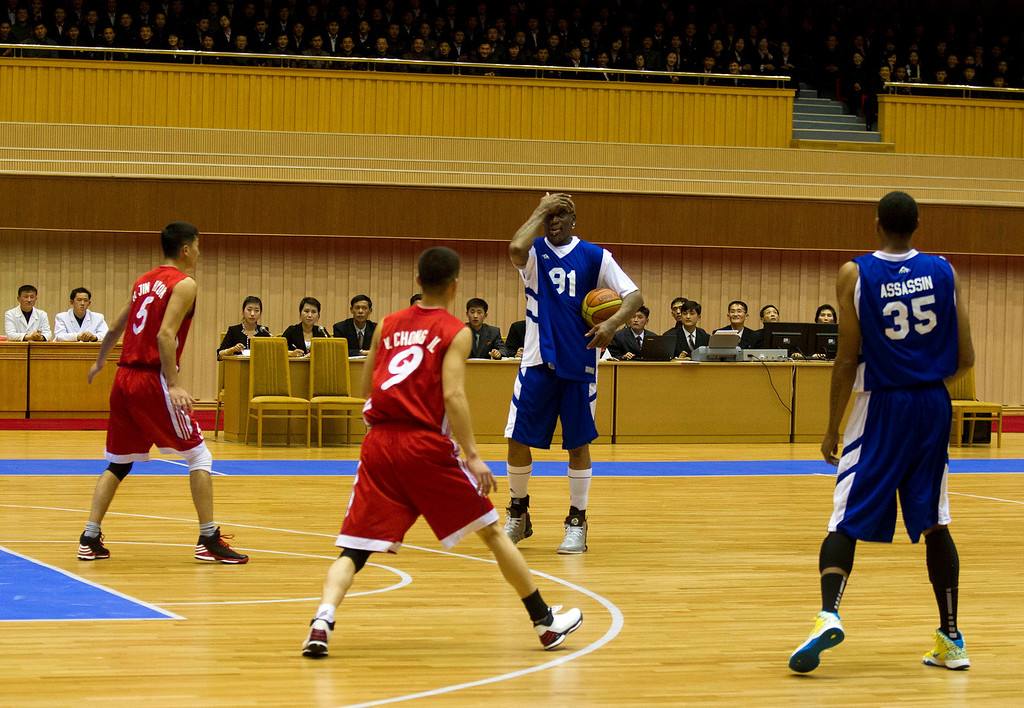 . Dennis Rodman, center, pauses with the ball during an exhibition basketball game with U.S. and North Korean players at an indoor stadium in Pyongyang, North Korea on Wednesday, Jan. 8, 2014. (AP Photo/Kim Kwang Hyon)