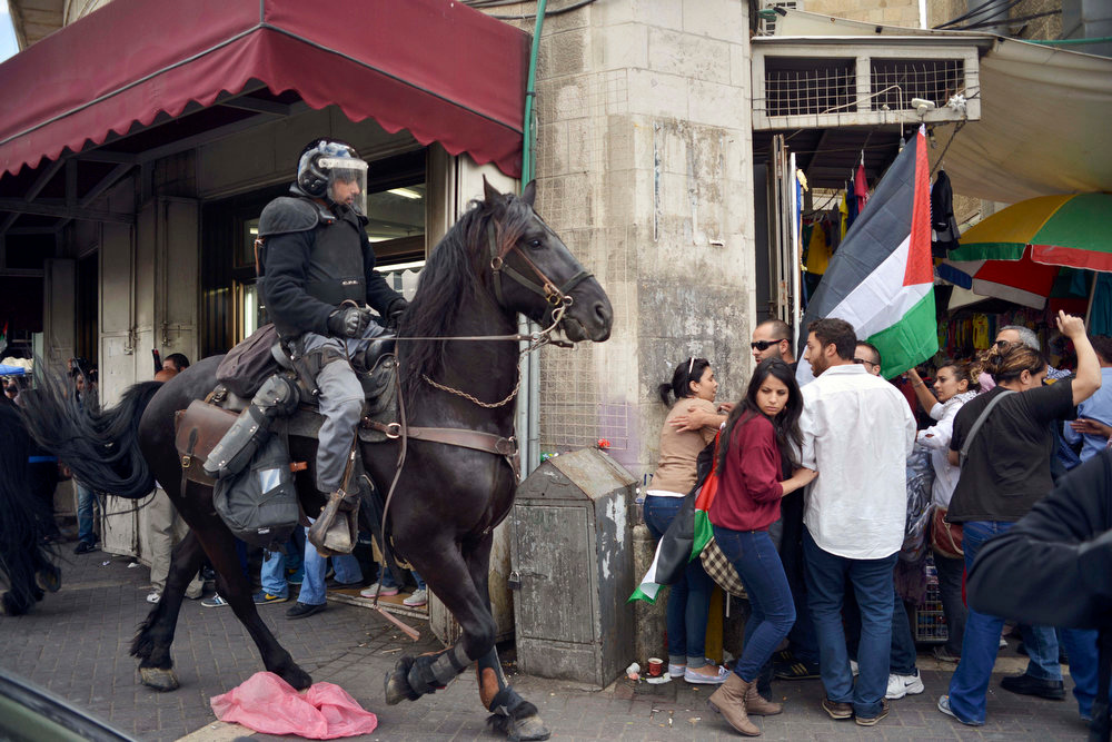 ". People move away from an Israeli policeman on a horse as Palestinians mark Nakba Day in Jerusalem, Wednesday, May 15, 2013. Palestinians annually mark the ""nakba,\"" or \""catastrophe\"" - the term they use to describe their defeat and displacement in the war that followed Israel\'s founding in 1948. (AP Photo/Mahmoud Illean)"
