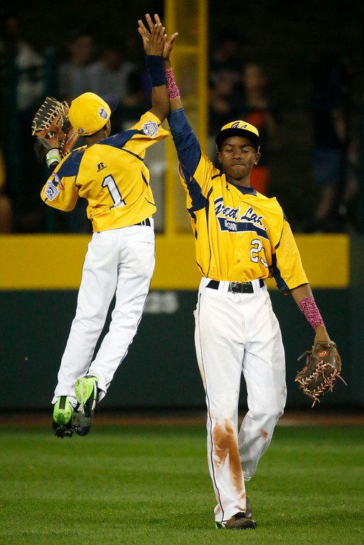 . Chicago\'s DJ Butler (1) celebrates with Pierce Jones (23) after Jones caught the final out of a 6-5 win over Philadelphia in an elimination baseball game at the Little League World Series tournament in South Williamsport, Pa., Thursday, Aug. 21, 2014. (AP Photo/Gene J. Puskar)