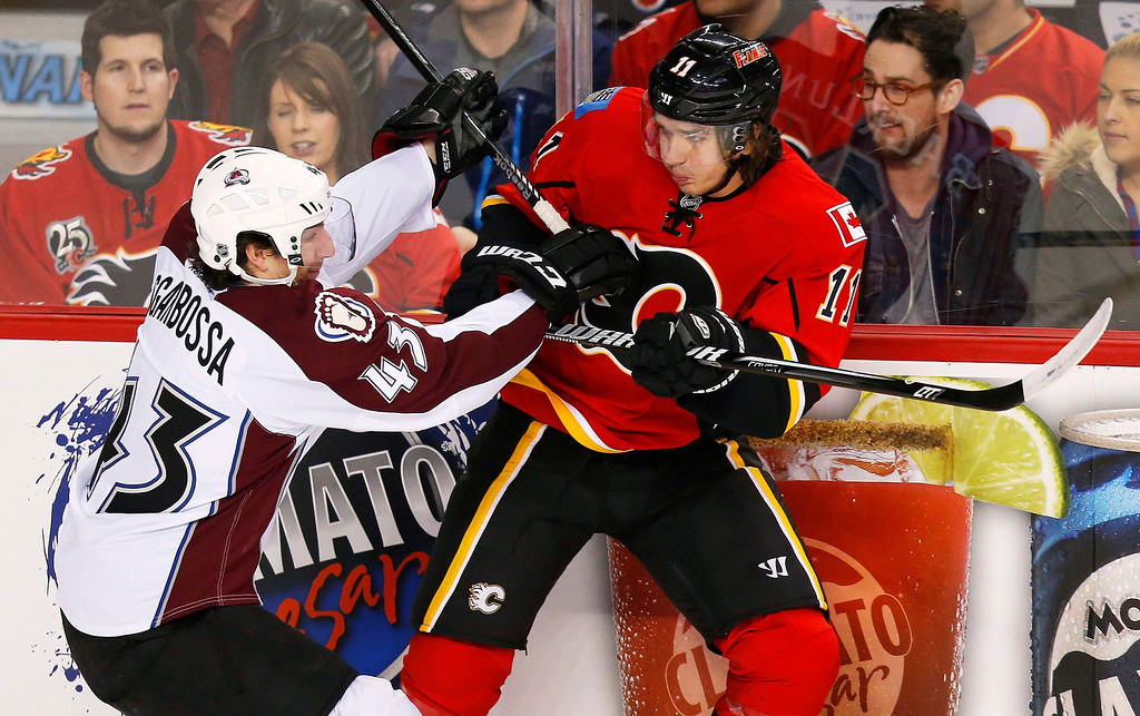 . Colorado Avalanche\' Michael Sgarbossa (L) hits Calgary Flames\' Mikael Backlund against the boards during the first period of their NHL hockey game in Calgary, Alberta, January 31, 2013. REUTERS/Todd Korol
