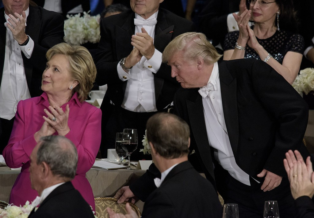 . Republican presidential nominee Donald Trump moves Democratic presidential nominee Hillary Clinton\'s chair  during the Alfred E. Smith Memorial Foundation Dinner at Waldorf Astoria October 20, 2016 in New York, New York. (BRENDAN SMIALOWSKI/AFP/Getty Images)
