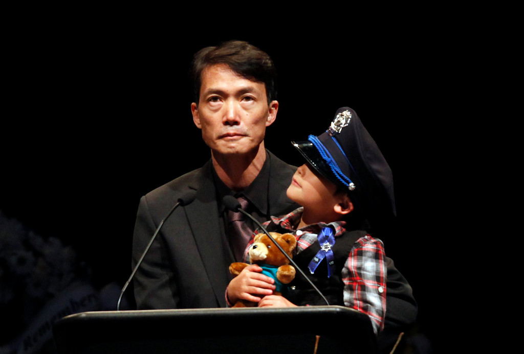 . Detective Elizabeth Butler\'s son, 5-year-old Joaquin Wu, clutches his teddy bear and wears his mother\'s hat as his father eulogizes the slain Santa Cruz police officer during memorial services at the HP Pavilion on Thursday, March 7, 2013 in San Jose, Calif.  (Karl Mondon/Bay Area News Group)