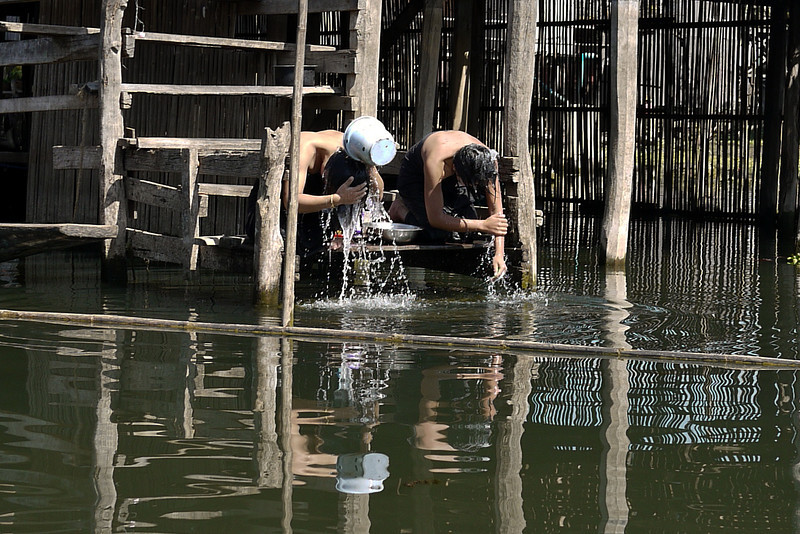 Two women use their longyi to protect their modesty as they bath on Inle Lake, Burma (Myanmar).
