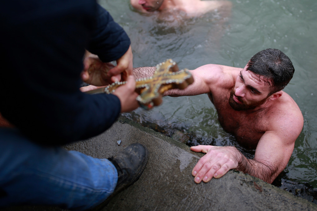 . Nicolaos Solis, 29, from Greece holding the wooden cross which was thrown into the waters by Ecumenical Patriarch Bartholomew I during the Epiphany ceremony to bless the waters at the Golden Horn in Istanbul, gets ashore, Friday, Jan. 6, 2017. (AP Photo/ Emrah Gurel)