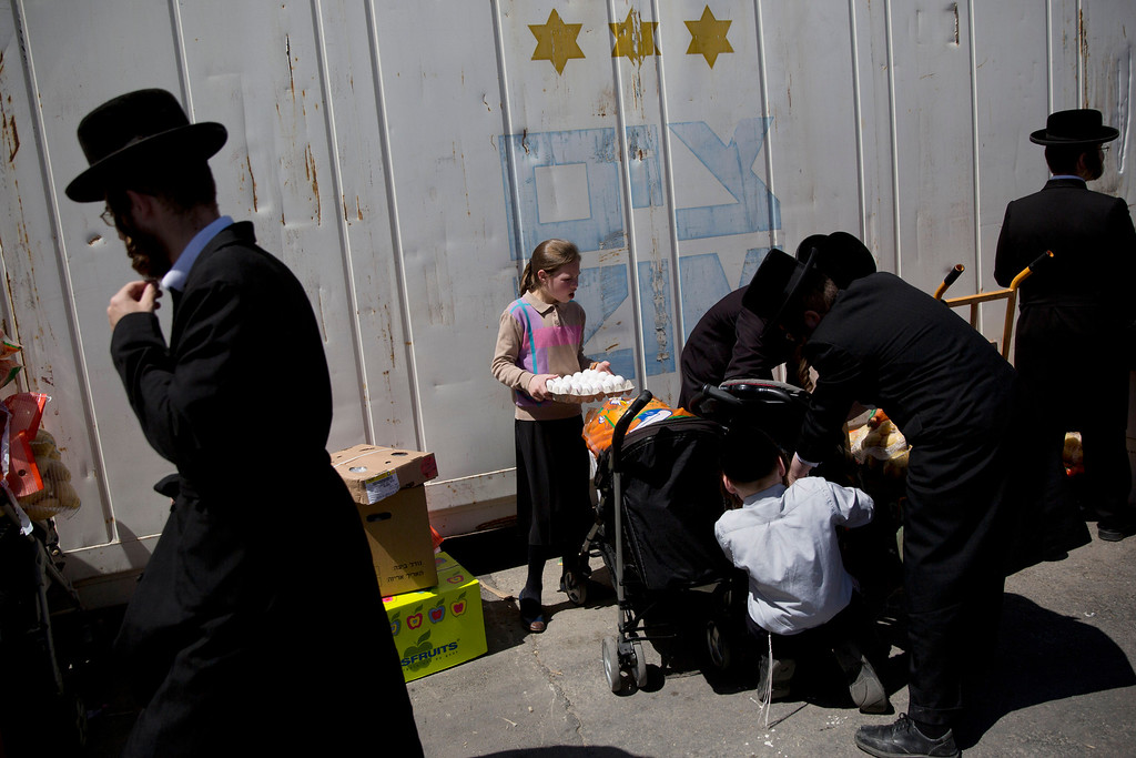 . Ultra-Orthodox Jews collect food distributed to large families for free, in a special market ahead of the upcoming Passover holiday in Jerusalem, Tuesday, April 19, 2016. The week-long festival which commemorates the exodus of the ancient Hebrews from Egypt begins on Friday. (AP Photo/Oded Balilty)