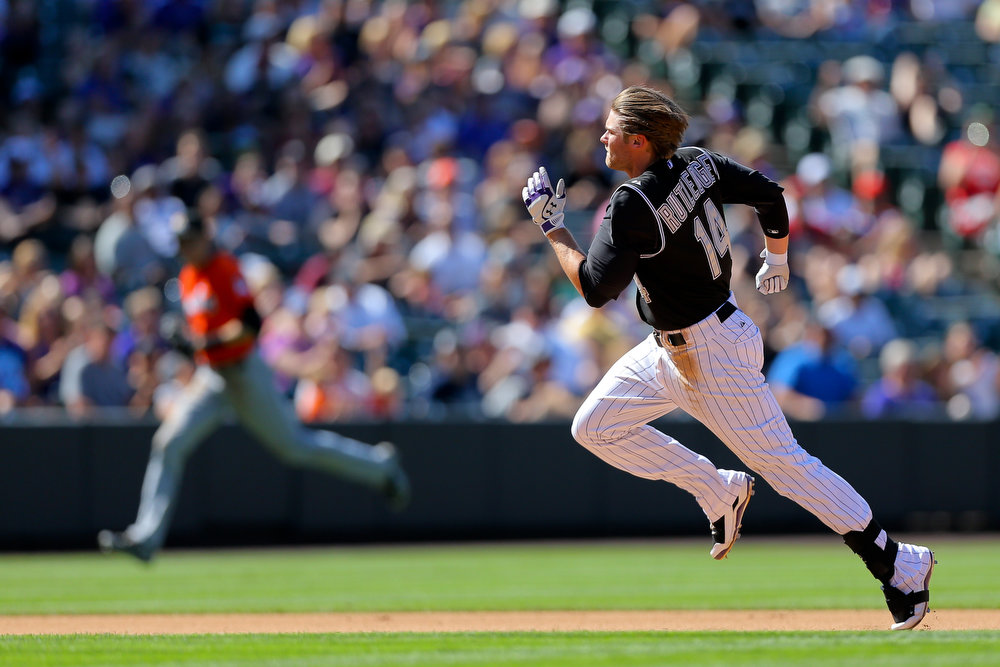 . Josh Rutledge #14 of the Colorado Rockies runs to third base on his way to a triple during the fourth inning against the Miami Marlins at Coors Field on August 24, 2014 in Denver, Colorado. The Rockies defeated the Marlins 7-4. (Photo by Justin Edmonds/Getty Images)