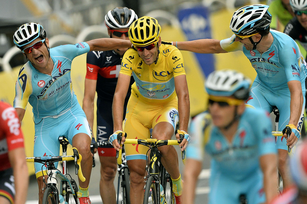 . 2014 Tour de France winner Italy\'s Vincenzo Nibali (C) is congratulated by Astana\'s teammates as he crosses the finish line on the Champs-Elysees avenue, at the end of the 137.5 km twenty-first and last stage of the 101st edition of the Tour de France cycling race on July 27, 2014 between Evry and Paris.  LIONEL BONAVENTURE/AFP/Getty Images