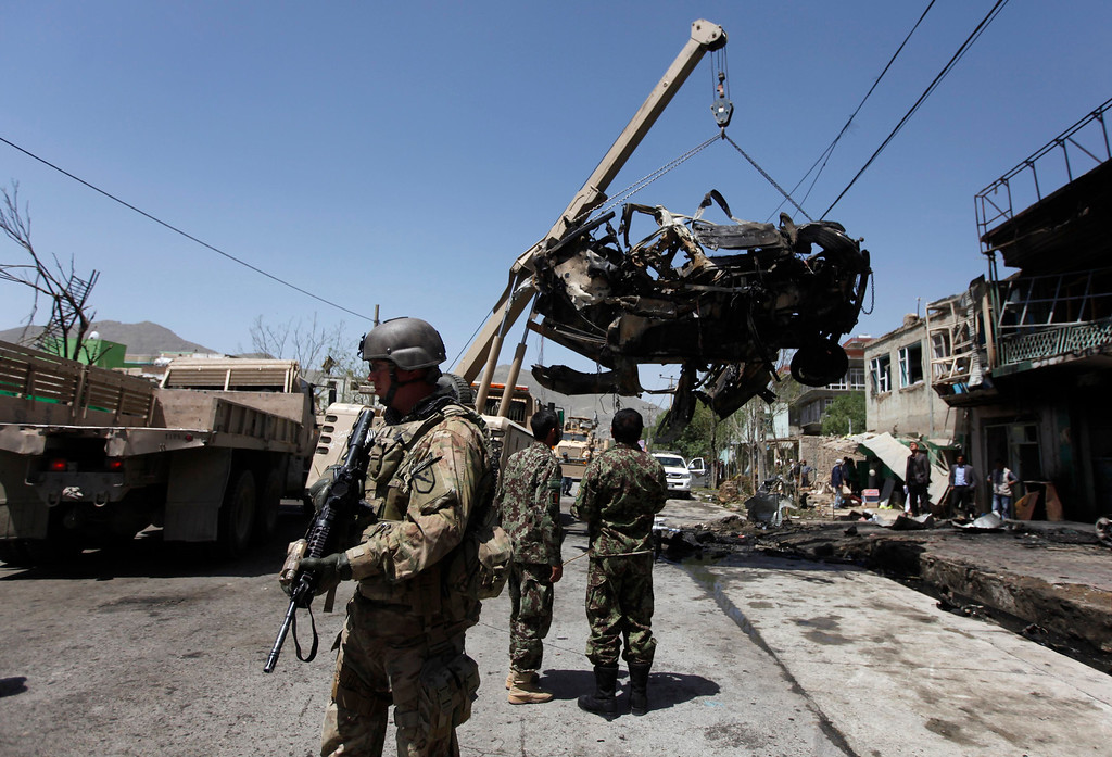 . A NATO soldier with the International Security Assistance Force (ISAF) stand at the site of a suicide attack in Kabul May 16, 2013. REUTERS/Mohammad Ismail