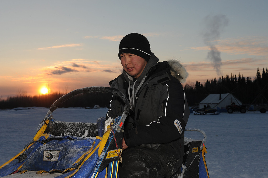 . Musher Mike Williams Jr. sits on his dog sled as he changes batteries in his headlamp at the Nikolai, Alaska, checkpoint during the Iditarod Trail Sled Dog Race at sunrise on Wednesday, March 5, 2014. (AP Photo/The Anchorage Daily News, Bob Hallinen)