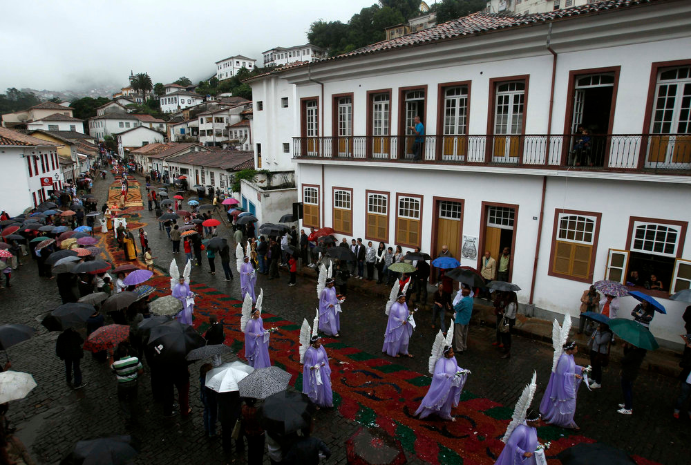 . Worshippers dressed as angels walk on special carpets made from colored saw dust and flowers during an Easter Sunday procession in the historic city of Ouro Preto in the Brazilian state of Minas Gerais, March 31, 2013. The streets of Ouro Preto are decorated with carpets made of colored saw dust and flowers, arranged in patterns to represent Biblical stories, during Holy Week. REUTERS/Pilar Olivares