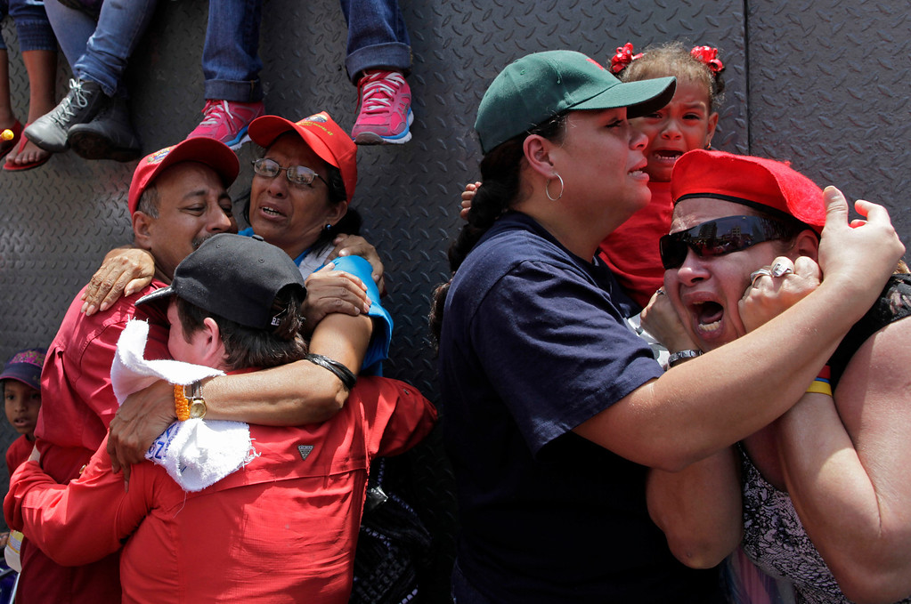 . Supporters of Venezuela\'s late President Hugo Chavez embrace as the coffin containing his body passes in the street as it is taken from the hospital, where he died on Tuesday, to a military academy where it will remain until his funeral in Caracas, Venezuela, Wednesday, March 6, 2013. Seven days of mourning were declared, all schools were suspended for the week and friendly heads of state were expected for an elaborate funeral Friday. (AP Photo/Rodrigo Abd)