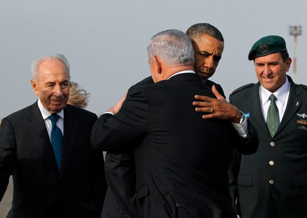 . U.S. President Barack Obama hugs Israeli Prime Minister Benjamin Netanyahu as President Shimon Peres (L) watches on, before Obama\'s departure from Tel Aviv International Airport, March 22, 2013.   REUTERS/Jason Reed