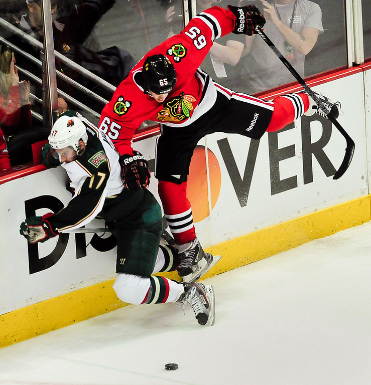 . Chicago Blackhawks center Andrew Shaw, right, gives Minnesota Wild left wing Torrey Mitchell a hard check in overtime. (Pioneer Press: Ben Garvin)