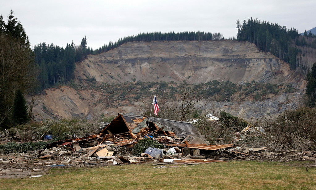 . A flag, put up by volunteers helping search the area, stands in the ruins of a home left at the end of a deadly mudslide from the now-barren hillside seen about a mile behind, Tuesday, March 25, 2014, in Oso, Wash.  (AP Photo/Elaine Thompson, File)
