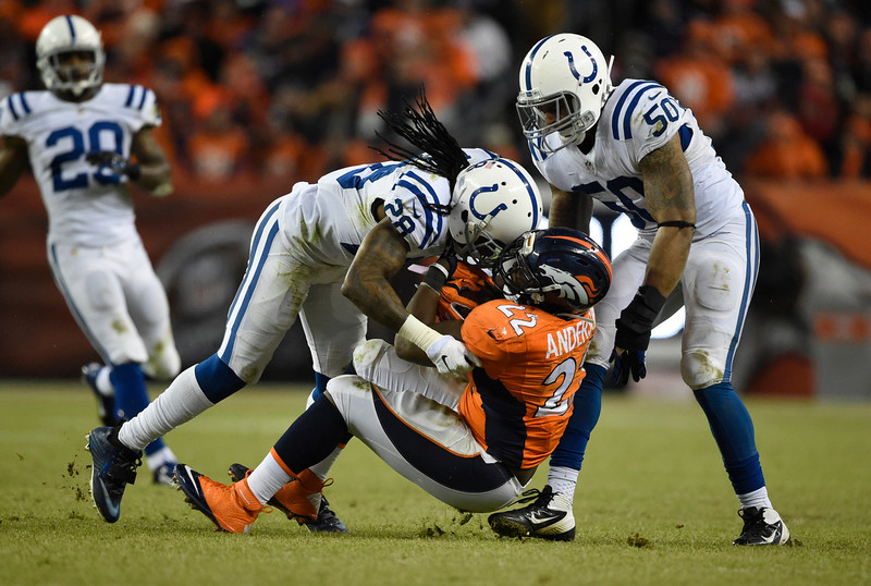 . Greg Toler (28) of the Indianapolis Colts takes down C.J. Anderson (22) of the Denver Broncos in the third quarter. The Denver Broncos played the Indianapolis Colts in an AFC divisional playoff game at Sports Authority Field at Mile High in Denver on January 11, 2015. (Photo by AAron Ontiveroz/The Denver Post)