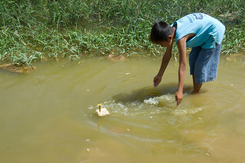 Orphan playing with a boat at a pond near the orphanage