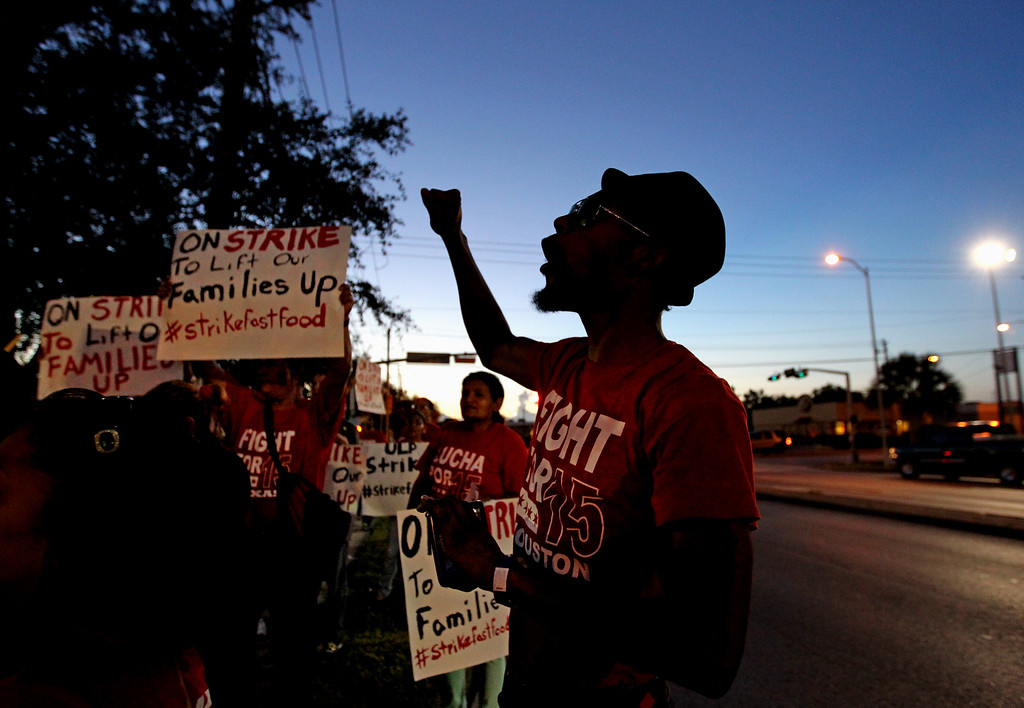 . Carlton Warren, right, an employee of Jack in the Box, leads members of the Fight for Fifteen coalition demanding $15 hourly wage march in front of a Jack in the Box restaurant at  5600 Gulfton Street Thursday, Sept. 4, 2014, in Houston, Texas. (AP Photo/Houston Chronicle, Gary Coronado)