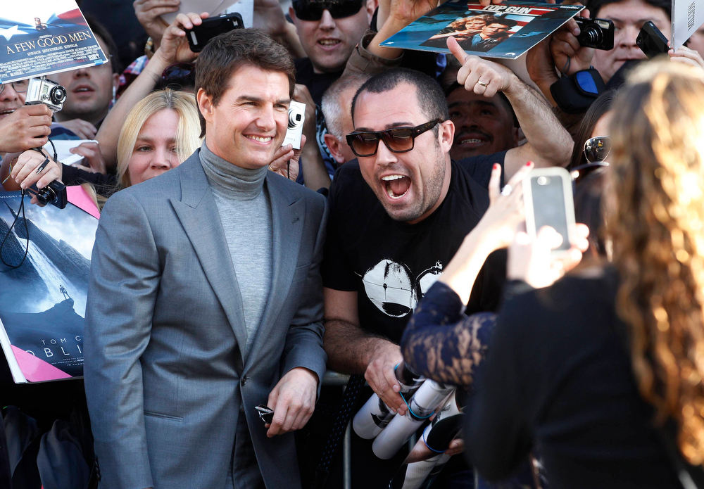 """. Actor Tom Cruise smiles as he poses with a fan along Hollywood Boulevard at the premiere of his new film \""""Oblivion\"""" in Hollywood April 10, 2013. REUTERS/Fred Prouser"""