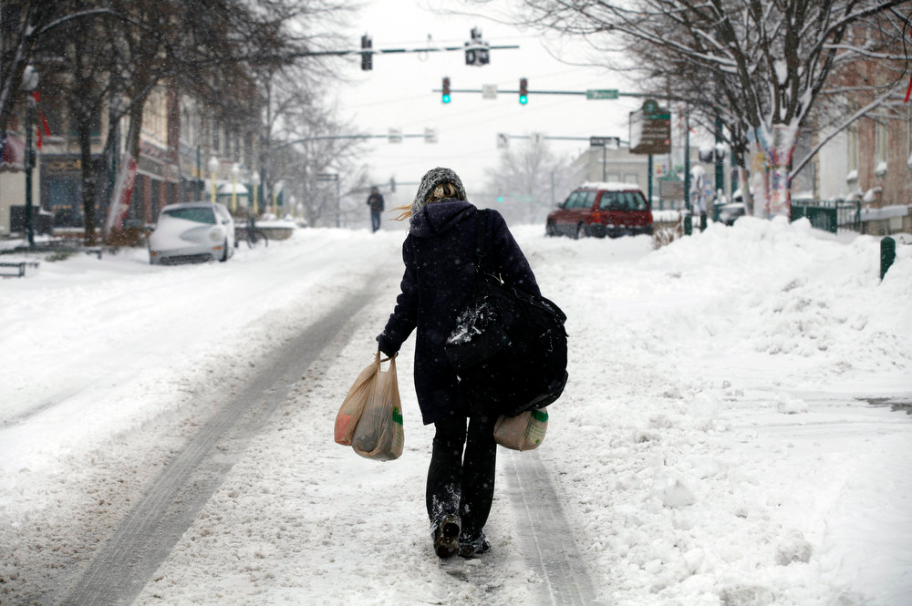 Description of . A woman carries groceries on snow covered Kirkwood, Wednesday, Dec. 26, 2012 in Bloomington, Ind. (AP Photo/Bloomington Herald-Times, Jeremy Hogan)