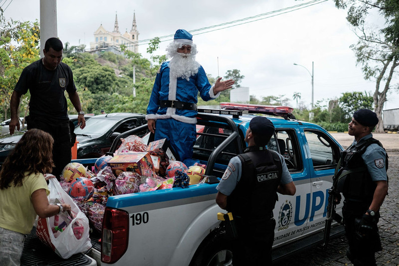 . A commander of the Pacified Police Units (UPPs) in a blue costume of Santa Claus delivers Christmas presents for children at Vila Cruzeiro favela (community) in Rio de Janeiro, Brazil, on December 24, 2014.  YASUYOSHI CHIBA/AFP/Getty Images