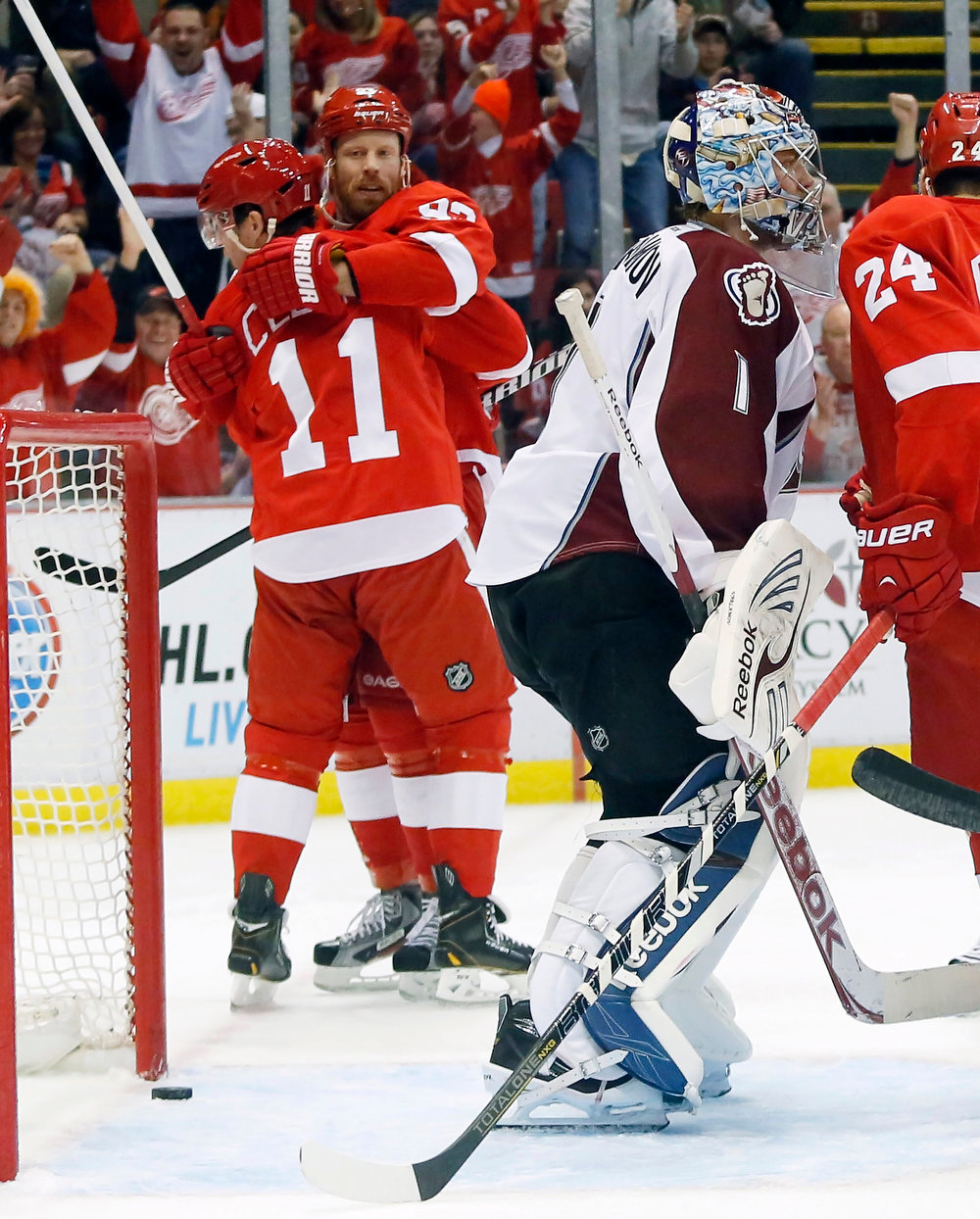 . Detroit Red Wings right wing Daniel Cleary (11) gets a hug from left wing Johan Franzen, of Sweden, after scoring on Colorado Avalanche goalie Semyon Varlamov (1), of Russia, in the second period of an NHL hockey game Monday, April 1, 2013, in Detroit. (AP Photo/Duane Burleson)