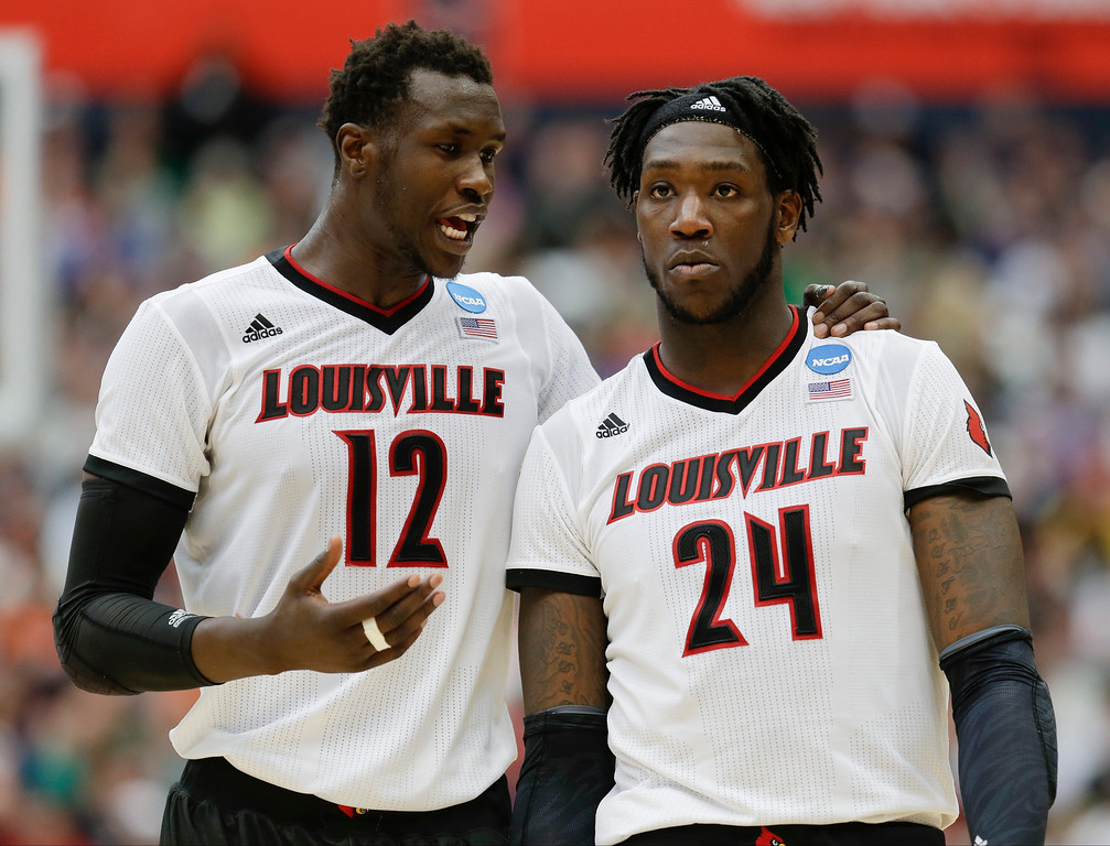 . Louisville\'s Mangok Mathiang (12), of Australia, talks to teammate Montrezl Harrell (24) during the second half of a regional final against Michigan State in the NCAA men\'s college basketball tournament Sunday, March 29, 2015, in Syracuse, N.Y. (AP Photo/Seth Wenig)
