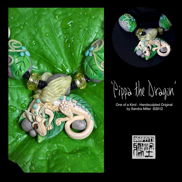 """PIPPA THE DRAGON-CLICK HERE TO VIEW VIDEO DESCRIPTION IN A NEW WINDOW      Pippa the Dragon is one of my favorite sculptures EVER , from her real German glass eyes to her iridescent wings ......and all the way down to her little rockgarden she's laying  in...This dragon diva is representin'!      Her body is sculpted in a beautiful ivory blend with tiny marbled turquoise nuggets of clay going down her spine. The expression on her face is so very very sweet and her body has a fun scaly texture!      The cluster of leaves Pippa is nestled in,  is surrounded with tiny granite pebbles, also sculpted from polymer clay, with one of the pebbles serving as a bail for the necklace cord to pass through.      Flanking each side of the main focal are two more hand sculpted boulders with leaves draping over their surface. The beads can be adjusted to ride higher or lower on the cord depending on your mood.   There are also two really pretty sparkly glass crystals with rivets in them, separating the dragon from the side pebbles     PENDANT MEASURES   2 1/2 x 2 1/2"""" Neoprene cord is finished at the back with chain and adjusts from 16-20"""" long"""