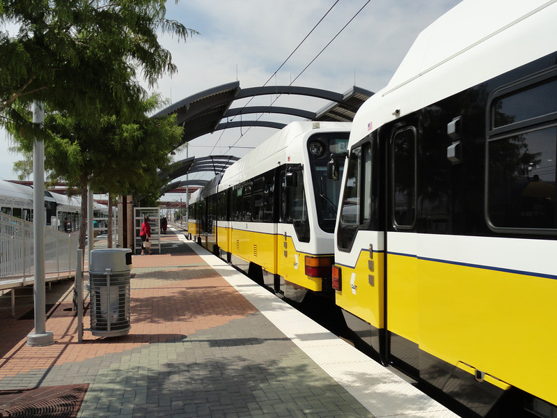 DART Light-Rail next to the Denton 'A' Train, Buses board on the other side of the LRV.