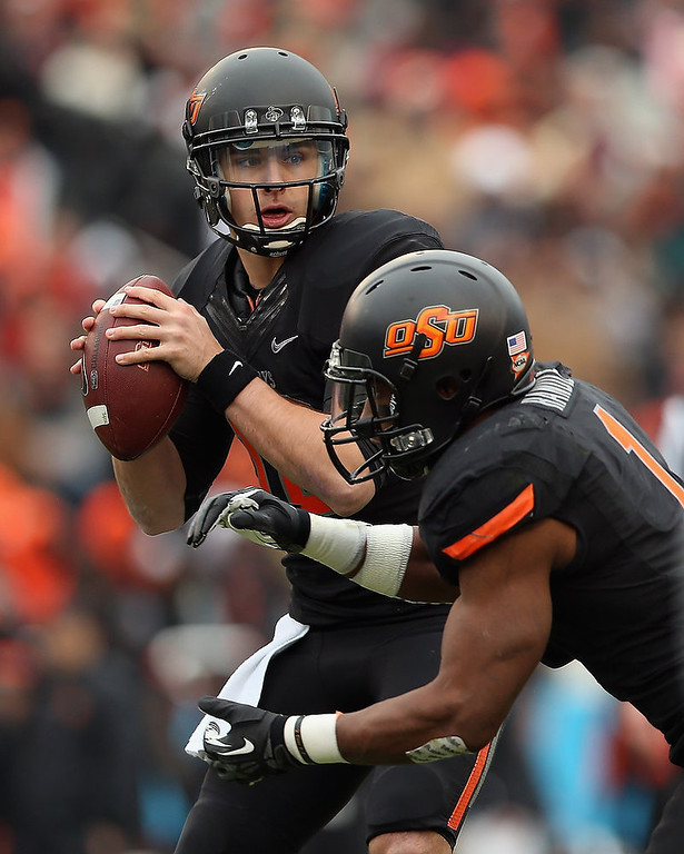 . Clint Chelf #10 of the Oklahoma State Cowboys passes against the Purdue Boilermakers during the Heart of Dallas Bowl at Cotton Bowl on January 1, 2013 in Dallas, Texas.  (Photo by Ronald Martinez/Getty Images)