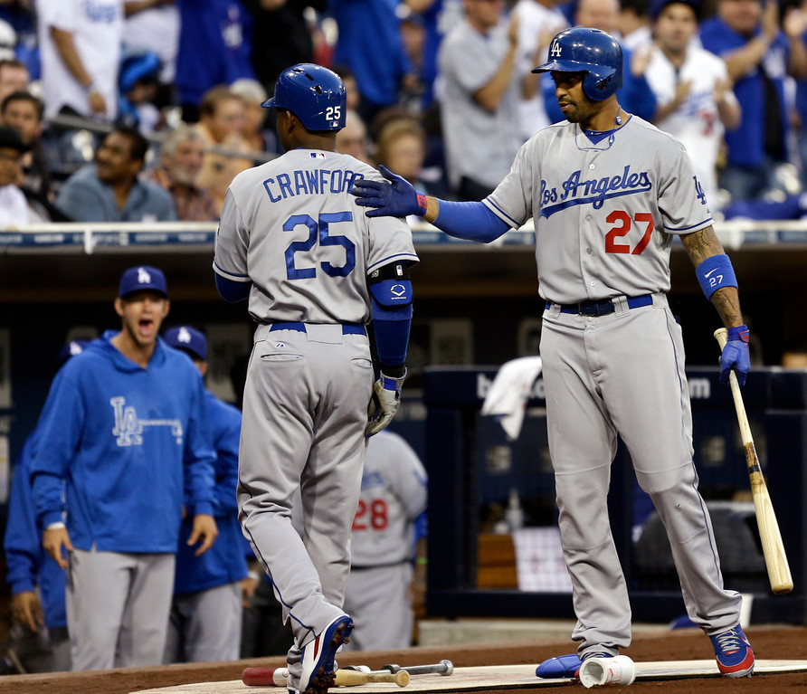 . Los Angeles Dodgers\' Carl Crawford gets a pat on the back from teammate Matt Kemp as heads to the dugout after leading off with a solo home run in the first inning of a baseball game against the San Diego Padres in San Diego, Wednesday, April 10, 2013. (AP Photo/Lenny Ignelzi)
