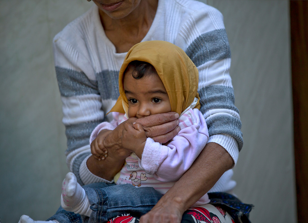 . A Roma woman holds a child during the eviction of more than 100 people from the homes they lived in Bucharest, Romania, Monday, Sept. 15, 2014. (AP Photo/Vadim Ghirda)