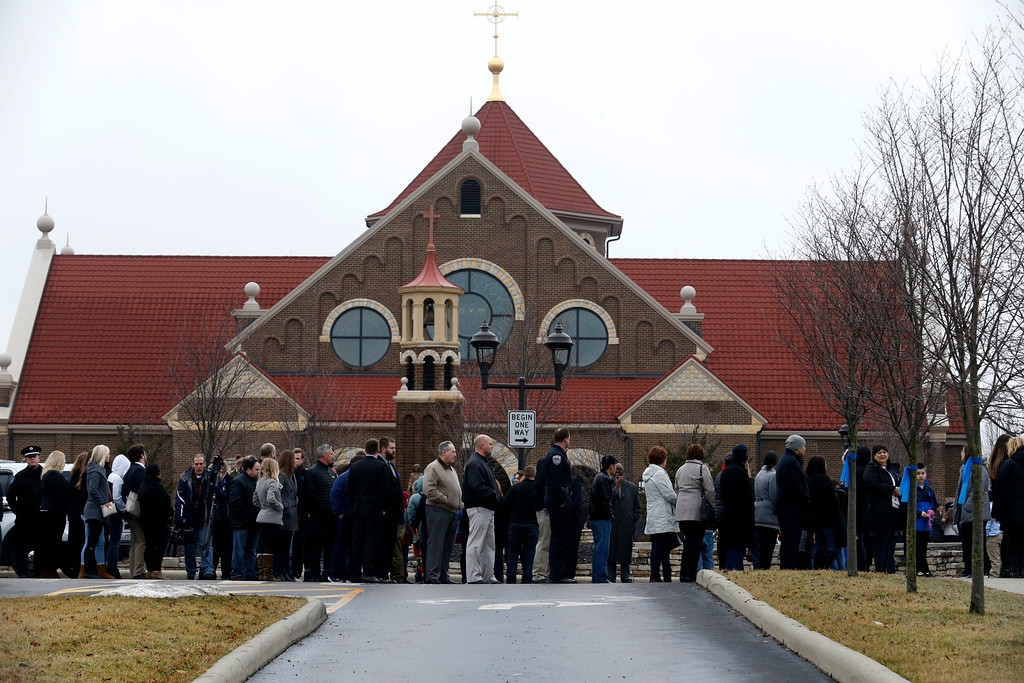 . Mourners line up outside St. Paul the Apostle Catholic Church in Westerville, Ohio, during the public viewing before funeral services for Westerville police officers Anthony Morelli and Eric Joering Friday, Feb. 16, 2018. The two veteran officers were shot after entering a residence on Saturday. The officers returned fire, wounding 30-year-old Quentin Smith, who has been charged with aggravated murder and remains hospitalized. (AP Photo/Paul Vernon)