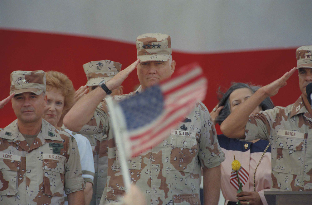 Description of . Gen. H. Norman Schwarzkopf salutes while a spectator waves a flag during welcome ceremonies Sunday morning at MacDill Air Force Base in Tampa, Fla., April 21, 1991. Schwarzkopf returned home after leading the allied victory in the Persian Gulf. (AP Photo/Lynne Sladky)
