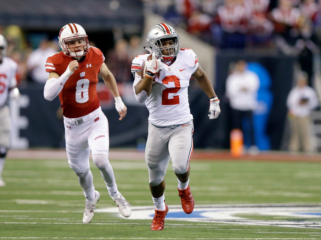 . Ohio State running back J.K. Dobbins, right, runs with the ball as Wisconsin safety Joe Ferguson gives chase during the first half of the Big Ten championship NCAA college football game, Saturday, Dec. 2, 2017, in Indianapolis. (AP Photo/Michael Conroy)