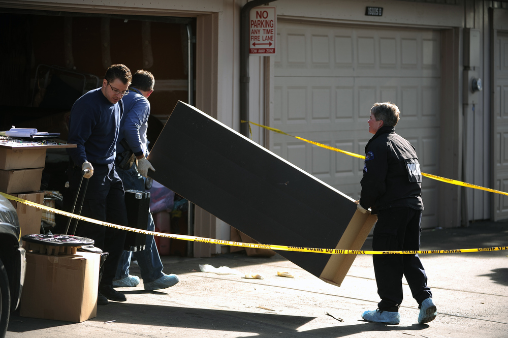 ". Aurora police and investigators look through the contents of the garage of the shooter as they continue to process the scene of the shootings at 16005 Ithaca place in Aurora today January 6th, 2013.   In what police officers called ""the worst-case scenario,\"" four people were found shot dead at a town home Saturday, including the gunman, who repeatedly fired at officers during a six-hour standoff. Helen H. Richardson, The Denver Post"