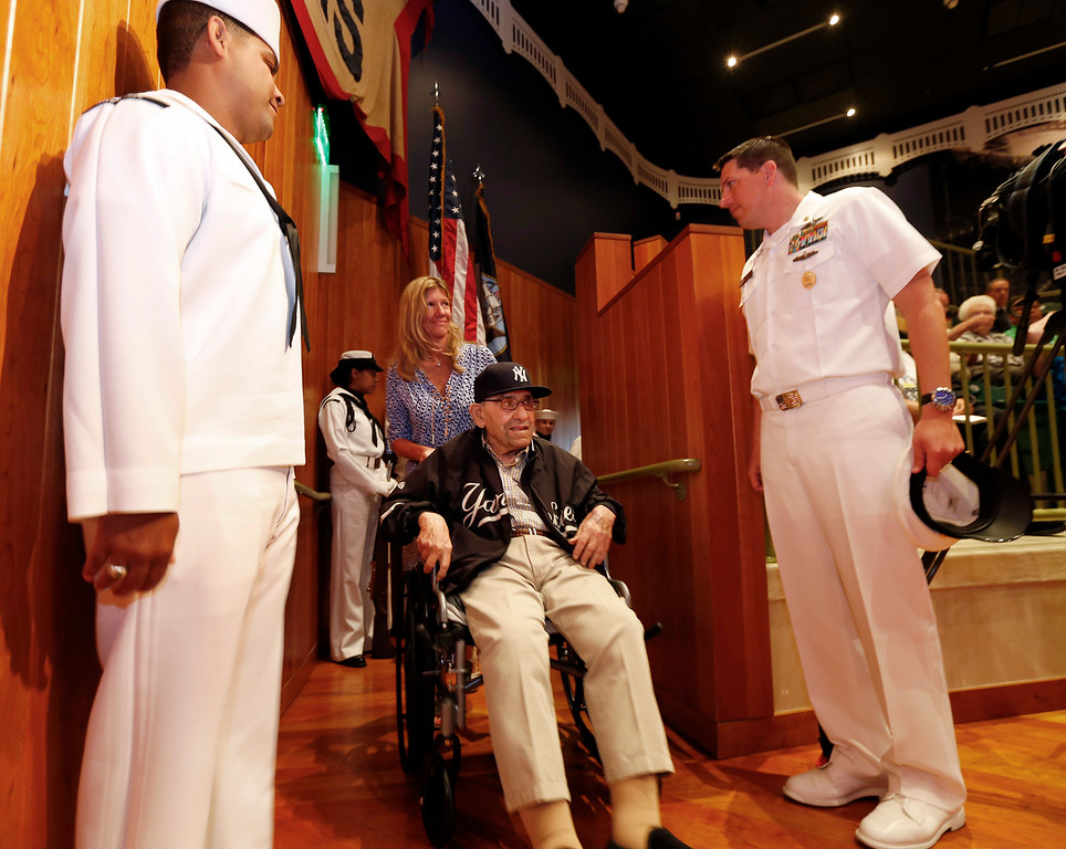 . Baseball Hall of Famer Yogi Berra enters, as he is honored by the U.S. Navy for his service 70 years ago during the D-Day Invasion, at a ceremony at the Yogi Berra Museum in Montclair, N.J.  on Friday, June 6, 2014. (AP Photo/Rich Schultz)
