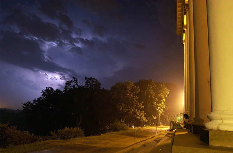 A Western Michigan University student watches an early morning lightning storm on the back steps of the historic East Hall on WMU's East Campus in Kalamazoo, Michiagn.