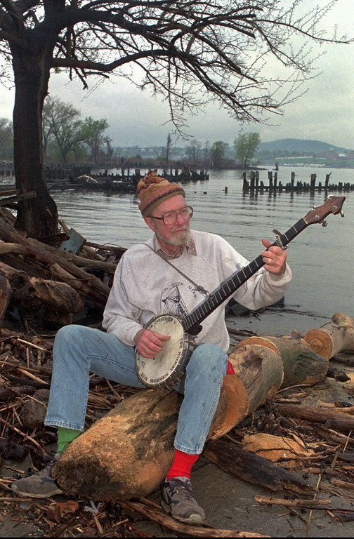 . SINGER, BANJO, HUDSON RIVER FOLK SINGER, SONGWRITER, SONG LEADER, PLAYING BANJO, SITTING ON LOG BY RIVER, WEARING TWO DIFFERENT COLORED SOCKS,