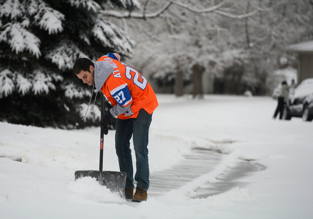 . Denver Broncos fan, Jesse Askeland, sporting a Steve Atwater jersey, clears his sidewalk Friday morning,  January 31, 2014. (Photo By Andy Cross / The Denver Post)