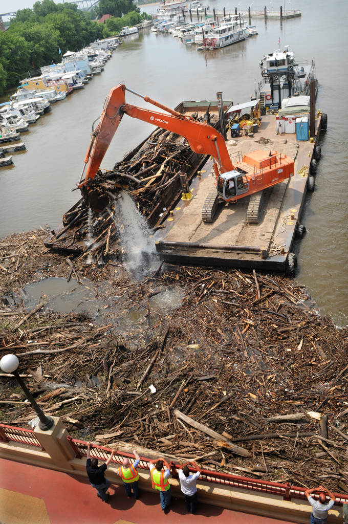 . Workers use a barge-mounted excavator to clean up a logjam that has collected on the Mississippi River in St. Paul on Friday, July 5, 2013. After severe storms seared through Minnesota in late June, fast-moving flood-stage water rushed logs, branches and garbage to the western edge of Raspberry Island, where it has collected. (Pioneer Press: Jean Pieri)