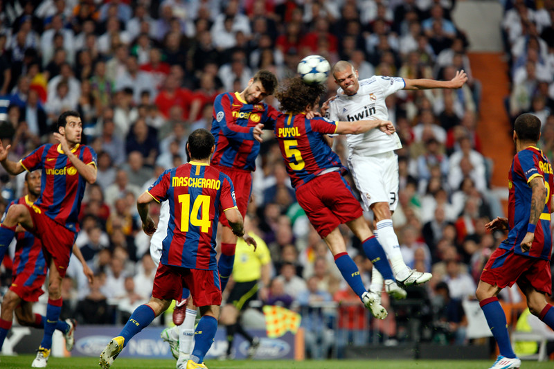 Pique, Puyol and Pepe trying to head the ball, UEFA Champions League Semifinals game between Real Madrid and FC Barcelona, Bernabeu Stadiumn, Madrid, Spain