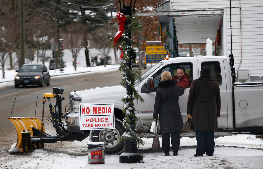 . A snowplow driver stops to give directions to two women in Newtown, Conn., Saturday, Dec. 14, 2013. Bells tolled 26 times to honor the children and educators killed one year ago in a shooting rampage at Sandy Hook Elementary School as local churches held memorial services. With snow falling and homes decorated with Christmas lights, Newtown looked every bit the classic New England town. But reminders of the private grief were everywhere.   (AP Photo/Robert F. Bukaty)