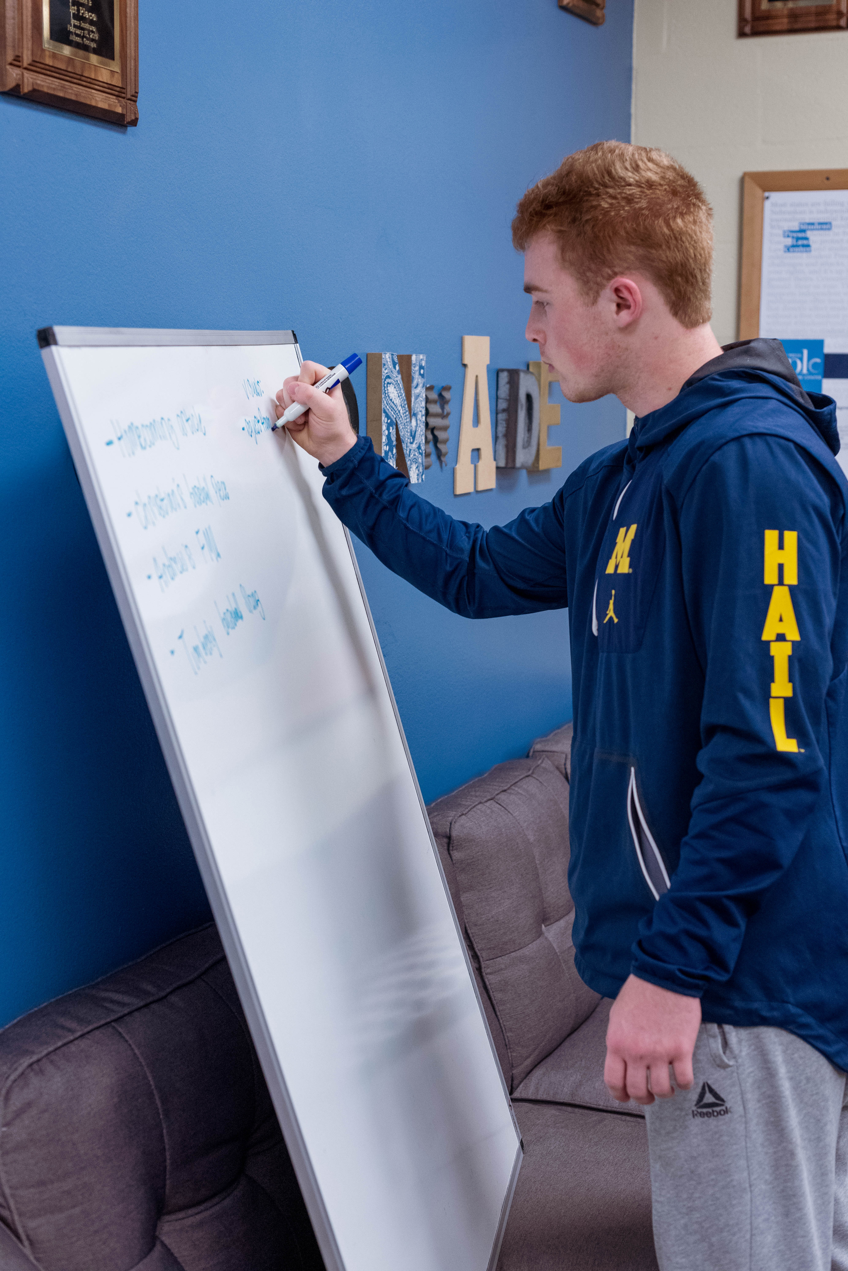 Sophomore Mass Communication major, Eric Boyd, uses the white board to layout a story for a future issue