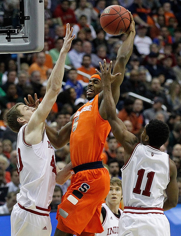 . Syracuse forward C.J. Fair (5) heads toward the basket under pressure from Indiana forward Cody Zeller (40) and guard Yogi Ferrell (11) during the first half of an East Regional semifinal in the NCAA college basketball tournament, Thursday, March 28, 2013, in Washington. (AP Photo/Alex Brandon)