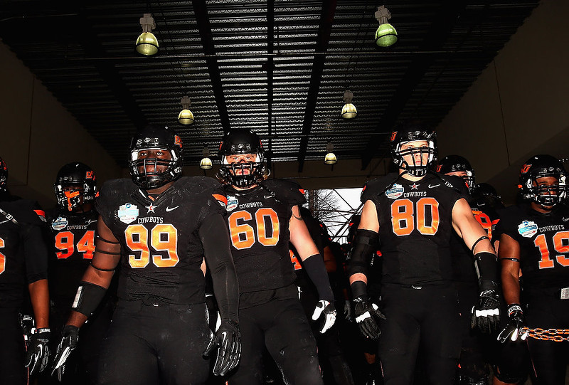 . The Oklahoma State Cowboys walk to the field before play against the Purdue Boilermakers during the Heart of Dallas Bowl at Cotton Bowl on January 1, 2013 in Dallas, Texas.  (Photo by Ronald Martinez/Getty Images)