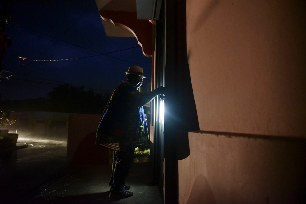 . A woman closes her property in the coastal area hours before the imminent impact of Maria, a Category 5 hurricane that threatens to hit the eastern region of the island with sustained winds of 165 miles per hour, in Naguabo, Puerto Rico, Tuesday, September 19, 2017. (AP Photo/Carlos Giusti)