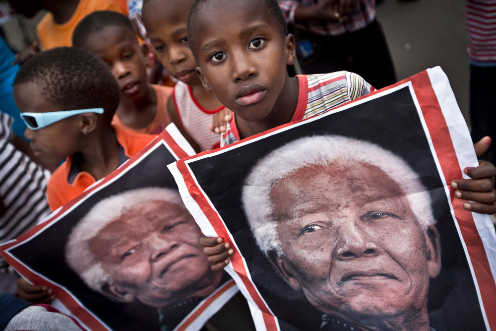 . South African children hold placards showing the face of Nelson Mandela as they celebrate his life, in the street outside his old house in Soweto, Johannesburg, South Africa, Friday, Dec. 6, 2013. Flags were lowered to half-staff and people in black townships, in upscale mostly white suburbs and in South Africa\'s vast rural grasslands commemorated Nelson Mandela with song, tears and prayers on Friday while pledging to adhere to the values of unity and democracy that he embodied. (AP Photo/Ben Curtis)