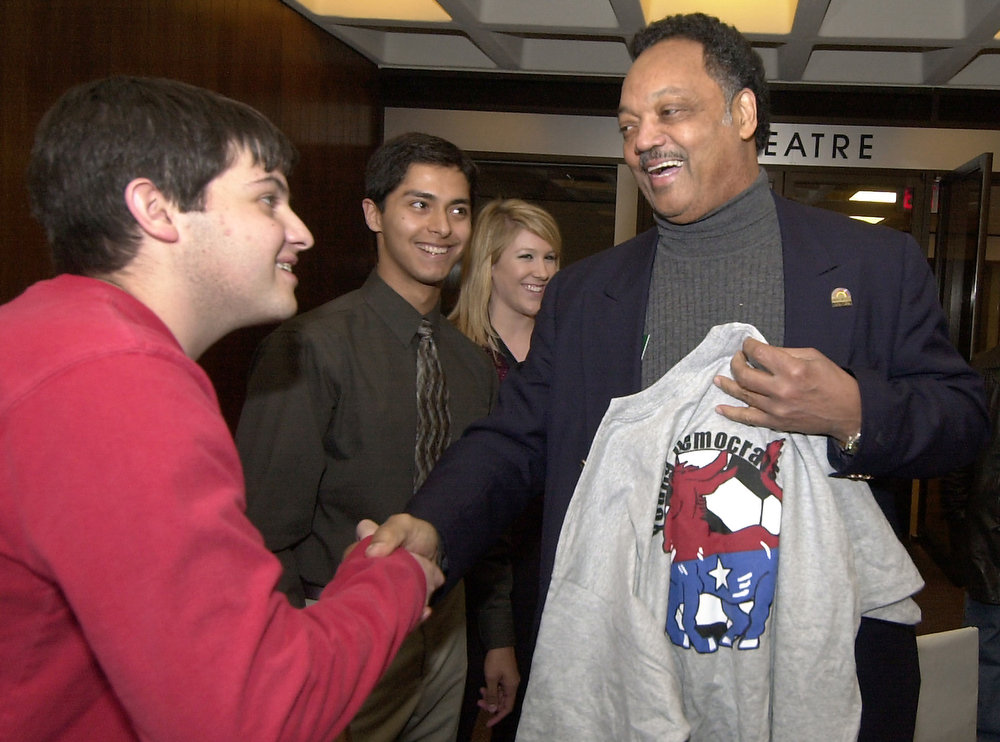 . The Rev. Jesse Jackson, right, shakes hands with Arkansas student Cody Bassham, far left, after Jackson accepted a t-shirt from the Young Democrats student organization in Fayetteville, Ark., Tuesday, Feb. 10, 2004. Jackson is scheduled to give a talk Tuesday night on the campus as part of the university\'s Black History Month celebration. Looking on are students Alejandro Aviles, center left, and Brittany Starr. (AP Photo/April L. Brown)