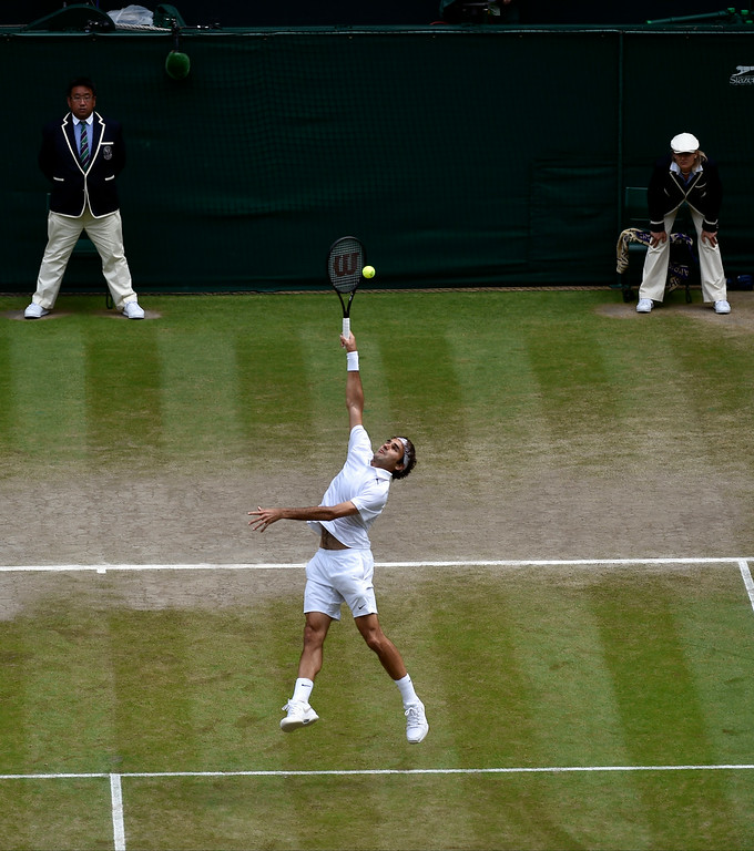 . Roger Federer of Switzerland stretches full length to play a return to Novak Djokovic of Serbia during the men\'s singles final at the All England Lawn Tennis Championships at Wimbledon, London, Sunday, July, 6, 2014. (AP Photo/Toby Melville, Pool)